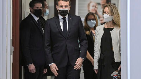 French President Emmanuel Macron, center, arrives for a meeting during a visit at the headquarters of the local CAF (French…