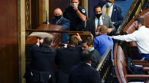 U.S. Capitol Police with guns drawn stand near a barricaded door as protesters try to break into the House Chamber at the U.S…