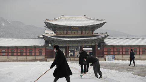 People wearing face masks as a precaution against the coronavirus clear snow at the Gyeongbok Palace, one of South Korea's well…
