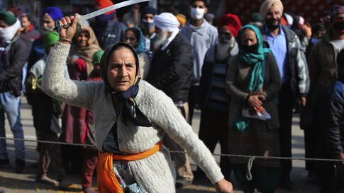 An Indian Sikh woman displays traditional martial art skills during a religious procession ahead of the birth anniversary of…