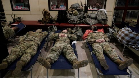National Guard troops sleep inside the Capitol Visitor's Center at the Capitol in Washington, Monday, Jan. 18, 2021. (AP Photo…