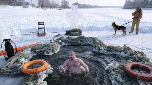 A man bathes in ice water during a traditional Epiphany celebration as the temperature dropped to about -20 degrees (-4 degrees…