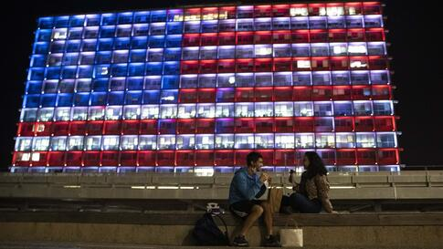 An Israeli couple sits near the Tel Aviv municipality building as it is lit up with the flag of the United States in Tel Aviv,…