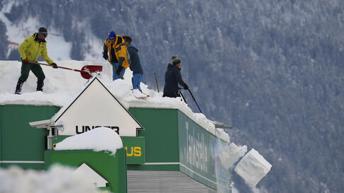 People clean the roof of a petrol station from snow, in Lienz, Austria, Monday, Jan. 4, 2021. (AP Photo/Matthias Schrader)