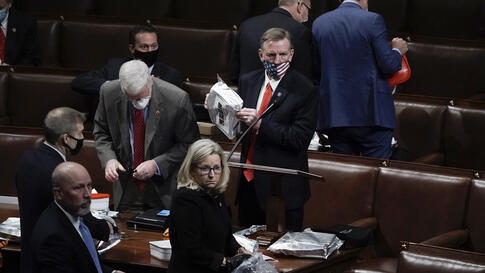 Rep. Paul Gosar, R-Ariz., center, and other lawmakers prepare to evacuate the floor as protesters try to break into the House…