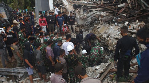 Rescuers search for survivors at the ruin of a government building collapsed during an earthquake in Mamuju, West Sulawesi,…