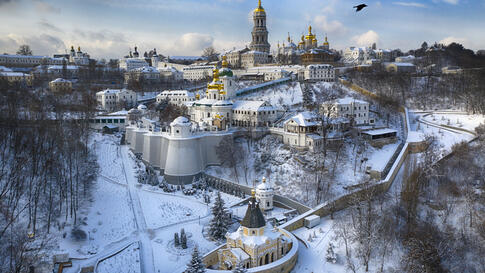 A bird flies over the sky near the 1000-year old Orthodox Monastery of Caves covered with the first snow this winter in Kyiv,…