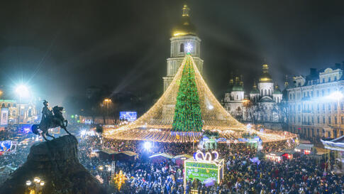 Crowds of people celebrate the New Year around the Christmas tree with the St. Sofia Cathedral in the background in Kyiv,…