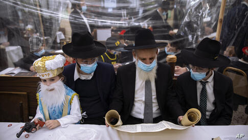 Jewish Ultra-Orthodox men and children, some wearing costumes and protective face masks, read the Book of Esther, which tells…