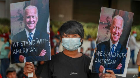 A demonstrators displays pictures of president Joe Biden during a protest against the military coup in Yangon, Myanmar,…