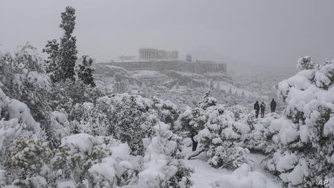People stand on Filopapos hill as snow falls with the ancient Acropolis hill and the Parthenon temple, in background, Athens,…