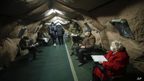 Over eighty-year-old wait to be administered a dose of the Pfizer/BioNTech vaccine, in a tent set up at the Baggio military…