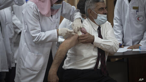Palestinian Health Ministry official Yahya Aabed, receives a shot of the COVID-19 Russian-made Sputnik V vaccine, in Gaza City,…