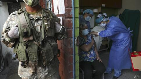 A soldier stands guard as a doctor gets a shot of the COVID-19 vaccine made by China's Sinopharm at a public hospital in Lima,…