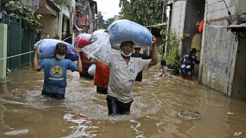 Indonesian men carry their belongings as they wade through the water at a flooded neighborhood following heavy rains in Jakarta…