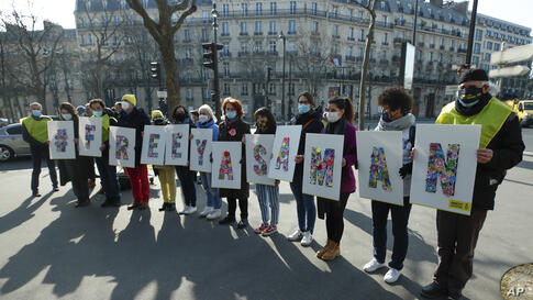 Human rights activists stage a protest with placards on a square near the Iranian embassy during Women' s Day in Paris, Monday,…