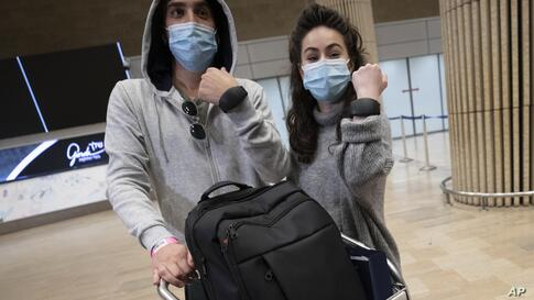 Israeli travelers hold up electronic monitoring bracelets they are required to wear after returning from abroad at the Ben…