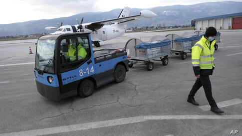 Boxes of the Pfizer vaccine are unloaded at the Sarajevo Airport, in Bosnia, Thursday, March 25, 2021. A plane carrying 24.000…