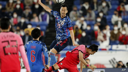 Japan's Maya Yoshida heads the ball over South Korea's Lee Jeong-hyeop during their friendly soccer match at Nissan Stadium in…