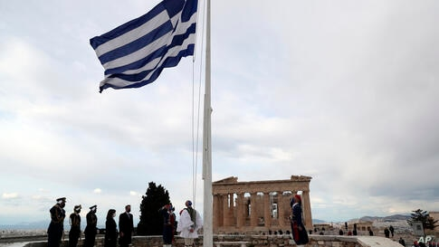 Members of the Presidential Guard raising the Greek flag in front of the Parthenon temple atop of Acropolis Hill as Greece's…