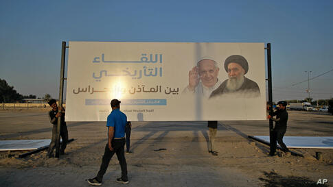 Iraqis put up a billboard announcing the upcoming visit of Pope Francis and his meeting with the revered Shiite Muslim leader,…