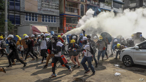 Anti-coup protesters run as one of them discharges a fire extinguisher to counter the impact of tear gas fired by riot…