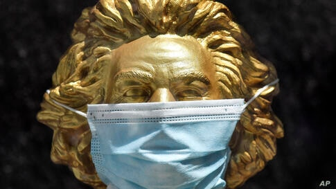 A golden bust shows Germany's most famous composer Ludwig van Beethoven with a medical face mask in a shopping window in Bonn,…