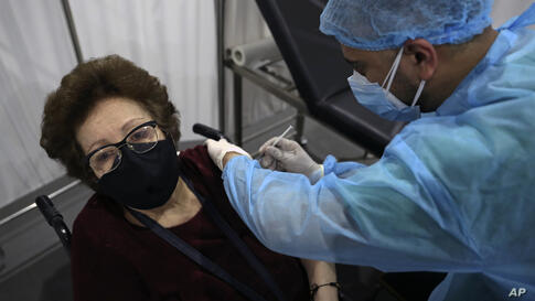 A woman receives a Pfizer COVID-19 vaccine at Saint George Hospital University Medical Center, in Beirut, Lebanon, Tuesday,…