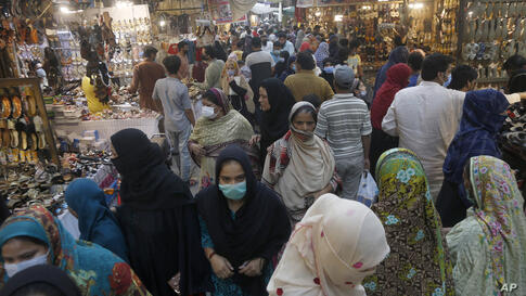 People ignore social distancing while shopping at a market after the government announced new restrictions to help control the…