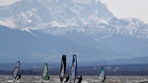 Surfers brave high winds to speed on the waves at lake Ammersee in front of Germanys highest mountain 'Zugspitze' near…