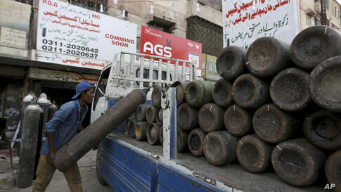 A worker loads oxygen cylinders on a truck which will supply private hospitals for COVID-19 patients, in Karachi, Pakistan,…
