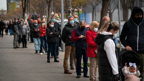 People line up outside a public ambulatory as they wait to receive a dose of the AstraZeneca vaccine in Barcelona, Spain,…