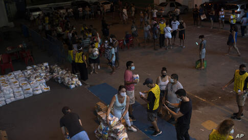 Residents receive food donated by the Bees of Love Institute during the COVID-19 pandemic in the Rocinha slum of Rio de Janeiro…