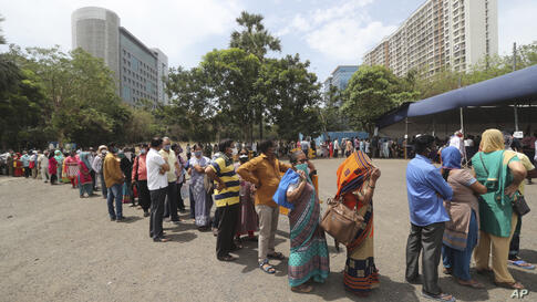 People queue up for COVID-19 vaccine in Mumbai, India, Thursday, April 22, 2021. New infections are rising faster in India than…