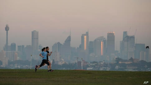 People exercise at a park as the sun rises in Sydney, Australia, Wednesday, April 28, 2021. (AP Photo/Mark Baker)