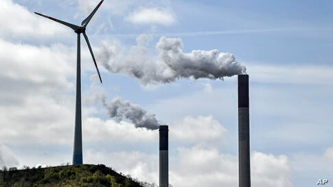 Chimneys of a coal-fired power plant smoke beside a wind turbine in Gelsenkirchen, Germany, Thursday, April 22, 2021. (AP Photo…