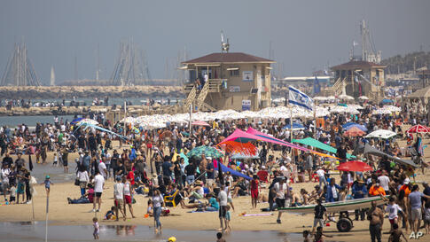 People flock to the beach after more than a year of coronavirus restrictions, during Independence Day celebrations, in Tel Aviv…
