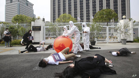 Environmental activists with an earth balloon stage a die-in during a rally, marking Earth Day against climate change in front…