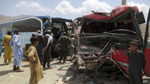 People stand near damaged buses after a deadly accident on the Kabul-Kandahar highway, on the outskirts of Kabul, Afghanistan,…