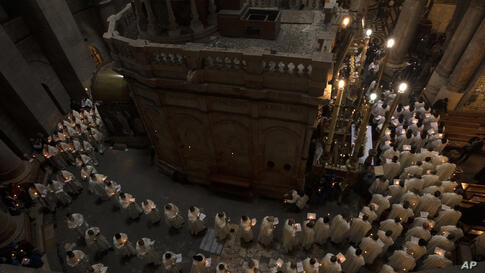 Priests circle the Holy Sepulchre during Holy Thursday mass led by the Latin Patriarch in the Old City of Jerusalem, Thursday,…