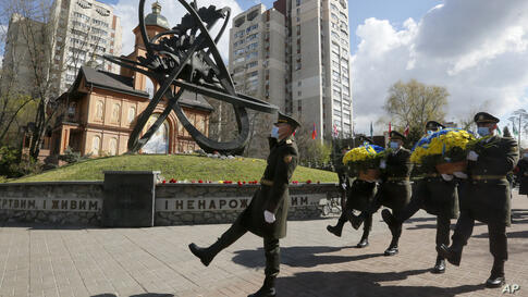 Guards of Honor march to lay a flower wreath at Chernobyl's victim monument in Ukraine's capital Kyiv, Ukraine, Monday, April…
