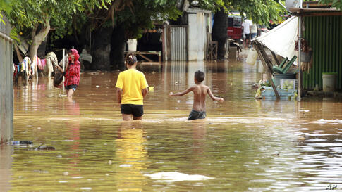 People wade through flood waters in Dili, East Timor, Monday, April 5, 2021. Multiple disasters caused by torrential rains in…
