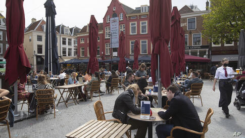Dutch customers eager for their first drink of coffee or something stronger at a cafe terrace have flocked to outdoor seating…