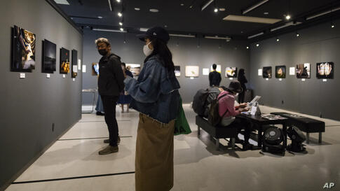 People wearing face masks to help curb the spread of the coronavirus visit a photography exhibition in Tokyo on Friday, April…