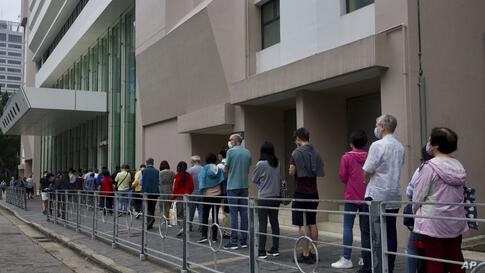 People queue outside a vaccination center for BioNTech in Hong Kong, Tuesday, April 6, 2021. Hong Kong have resumed…