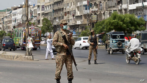 Army troops stand guard in a business district to observe new restrictions announced by government to help control the spread…