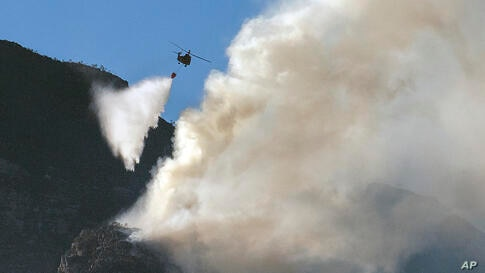 A South African military helicopter drops water on the top of Table Mountain in Cape Town, South Africa, Tuesday, April 20,…