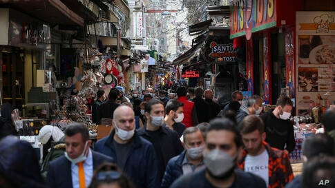 People walk near the historical Egyptian Bazaar, in Istanbul, Tuesday, April 13, 2021. As Muslims around the world began…