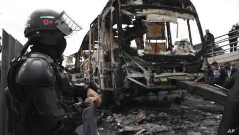A police officer stands guard by the charred remains of a public bus that was burned during an anti-government protest in San…