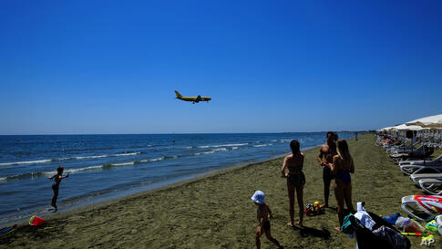 People on the beach as an aircraft prepares for landing at Larnaca international airport in the background, at Makenzi beach in…